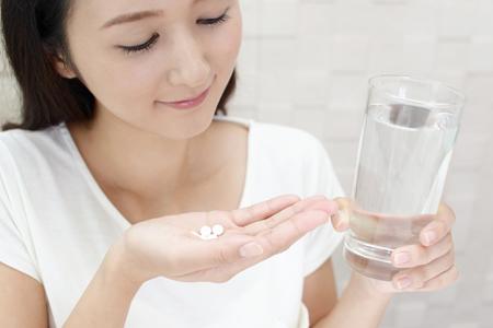 コラーゲンサプリメントを飲む女性の画像