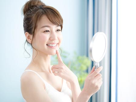 美容鍼(美顔鍼)の効果を確認する女性の画像