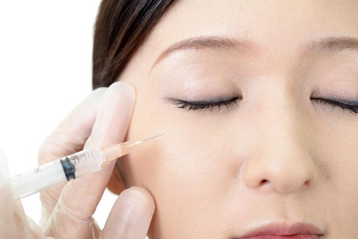 目の下のくぼみにヒアルロン酸注入する女性の画像