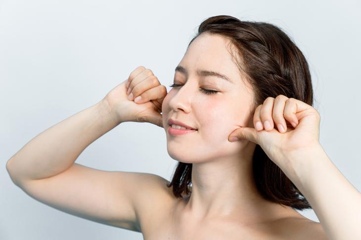 顔のたるみをとるためにツボを押す女性の画像
