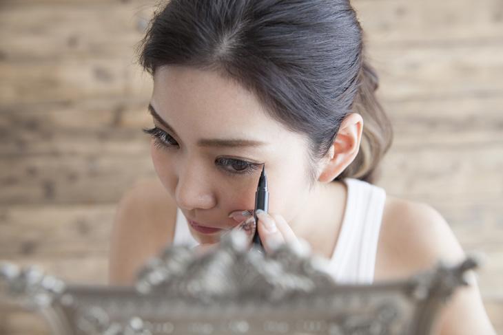 アイメイクをする女性の画像