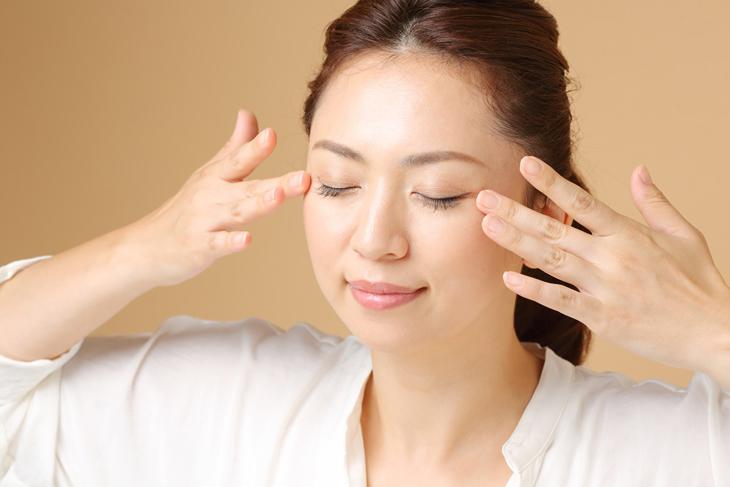 顔のたるみ解消にツボを押す女性の画像