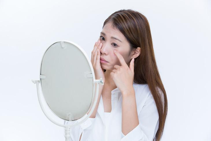 目元のしわをマッサージする女性の画像