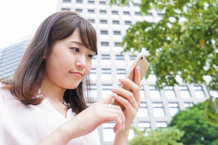 スマホを使う女性の画像
