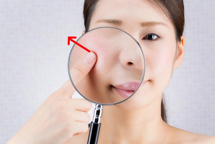 顔のたるみをチェックする女性の画像