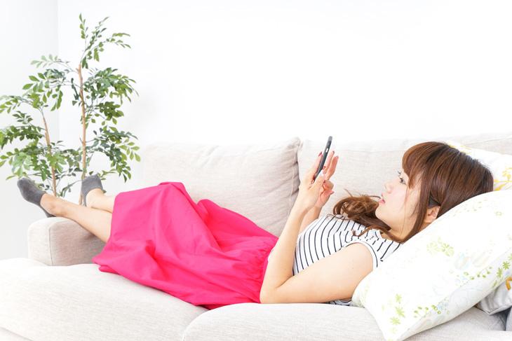 寝ながらスマホを使う女性の画像