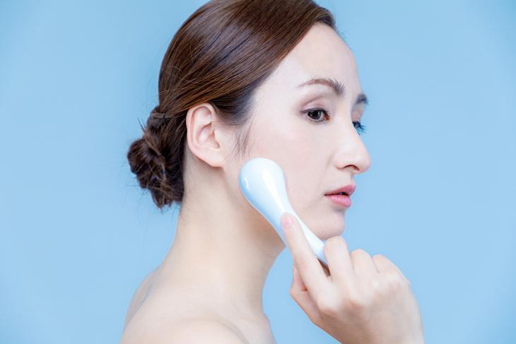 たるみ解消の美顔器を使う女性の画像