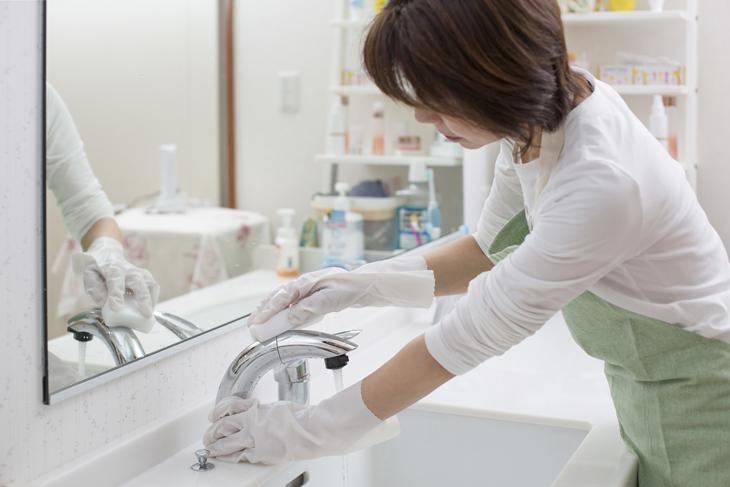 首を倒して掃除をする女性の画像