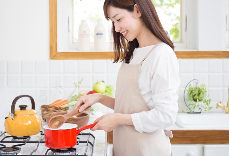 うつむいて料理をする女性の画像