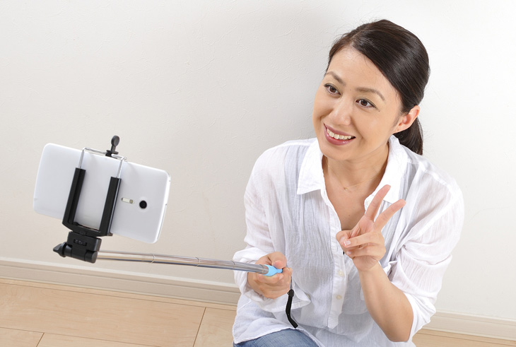 顔のたるみを写真でチェックする女性の画像