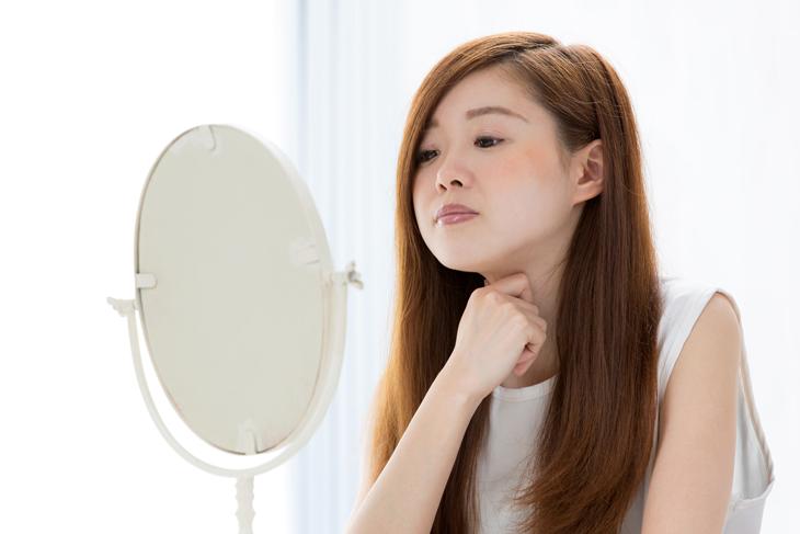 首をつまむ女性の画像