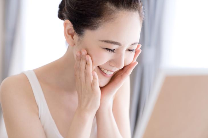 乾燥の改善のクリームを塗ってハンドプレスする女性の画像